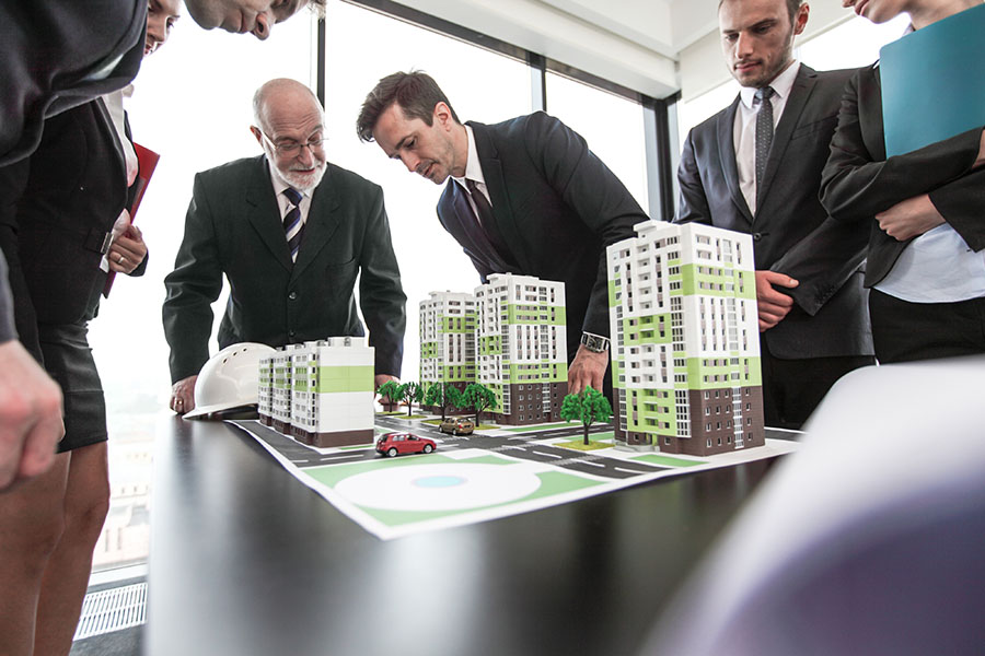 Business Insurance - Group of Businessmen Planning Construction of New Condo Buildings
