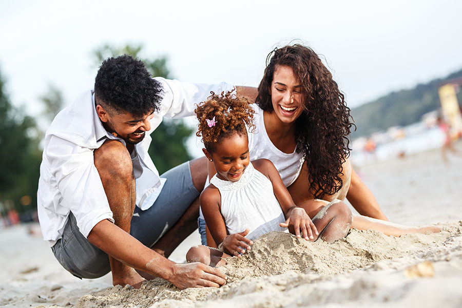 Personal Insurance - Happy Parents Playing on the Beach with Their Young Daughter